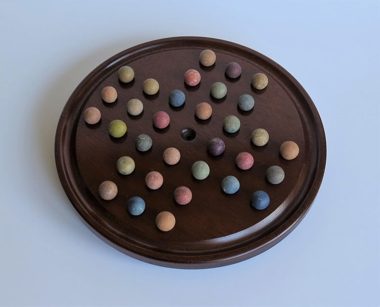 This is a complete Victorian board game of marble solitaire, with a lovely hand turned mahogany board and 32 early ceramic clay and stone hand made marbles, all dating to the 19th century.  The circular board has a larger than normal diameter of