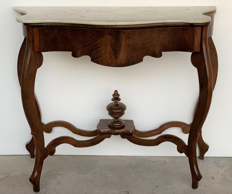 Walnut console table with four curved legs united by an urn stretcher beneath a marble top.
