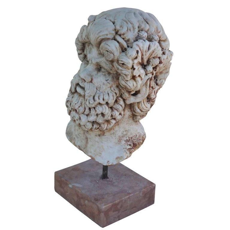 A mask of Asklepios the Greek god of healing. Hand carved in white Carrara marble and mounted on a Rosso Verona marble base, wear consistent with age and use, circa 19th century Verona, Italy.  A similar head is found in the Hermitage, Saint
