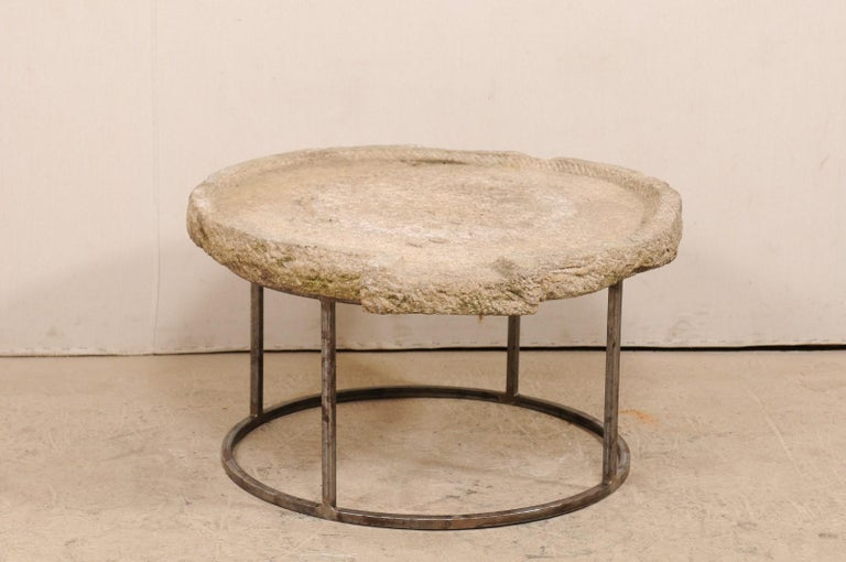 A 19th century Mediterranean stone trough table on custom base. This unique coffee table has been fashioned from a 19th century stone trough, once used in the production to press olives into oil. The round-shaped stone has been carved of hand and
