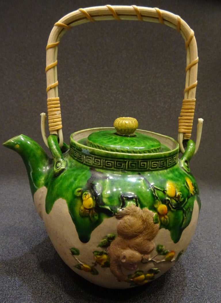 A very soughtafter piece of collection, a Meiji green ceramic teapot with monkeys and peachs in relief. With marks of Banko .Handle and top in bamboo. In a perfect condition with age and use. An exquisite piece.