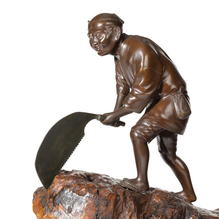 An attractive Meiji period bronze of a woodcutter sawing a large tree trunk, he is standing on top of the wooden trunk, raised at one end on a trestle, and sawing with a large semi-circular toothed saw, wearing traditional clothing and with a pouch