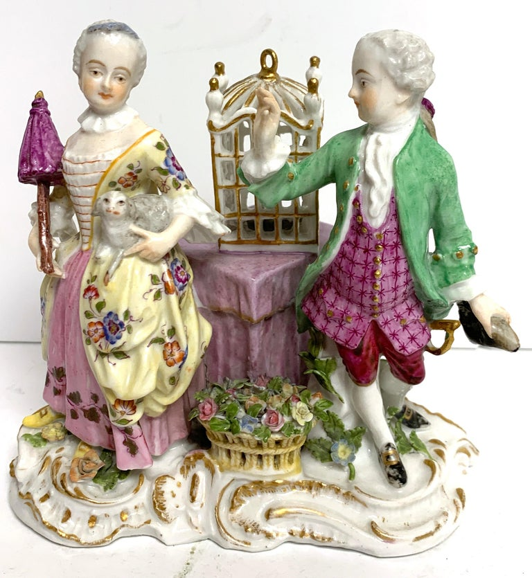 19th century Meissen Birdcage grouping, an unusual grouping, the double figure with a lady of the court holding a dog and a gentleman holding his hat in a interior with a birdcage on a table, with a basket of flowers at foot.