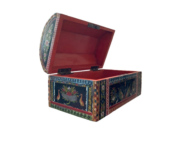 This chest from the 19th century is a majestic example of the technique known as 'maque', or lacquer, developed in Mexico over the centuries. It is lacquered in an orange background and profusely decorated on all sides. On its front a the ornament