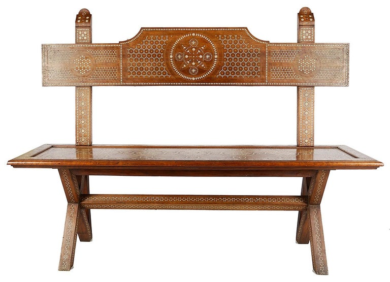 A good quality 19th century Italian, Milanese walnut bench in the Moorish style. Having classical inlaid motif decoration to the backrest and seat. Raised on two X-framed end supports, united by a stretcher between.