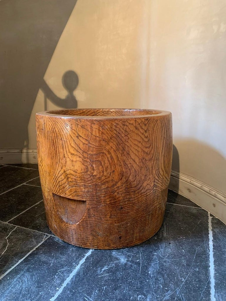 A large Chinese elm planter. The barrel shaped planter made from one solid piece of beautifully grained elm. Originally containers like this would have been used as measurement for grain. The incisions at the sides were for inserting a lifting