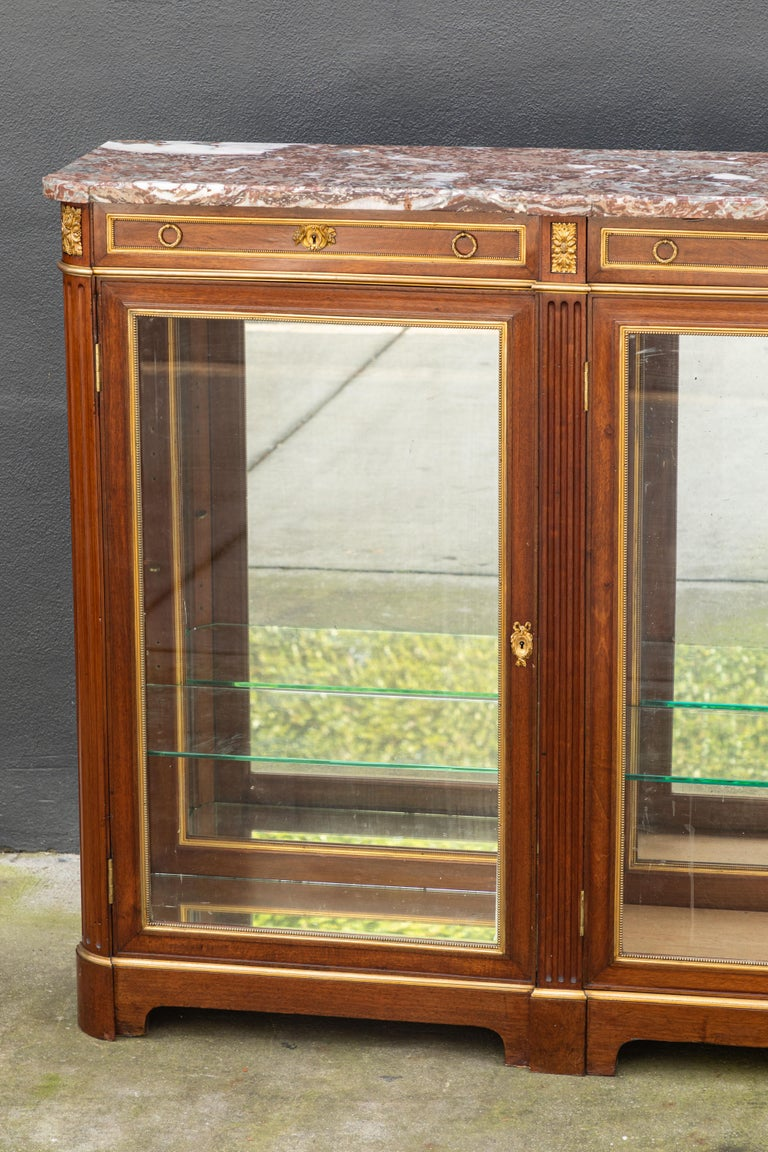 19th century monumental French bronze mounted bookcase/vitrine with glass shelves and mirrored back. The marble top is original to the piece.