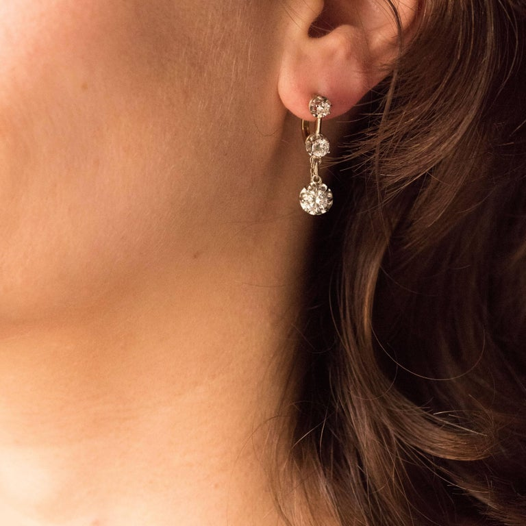 Earrings in 18 karats yellow and white gold, eagle's head hallmark. Sublime and elegant, each earring is composed of 3 brilliant-cut diamonds set with claws, falling. The clasp puts on from the front. Total weight of diamonds: about 1.95 carat.