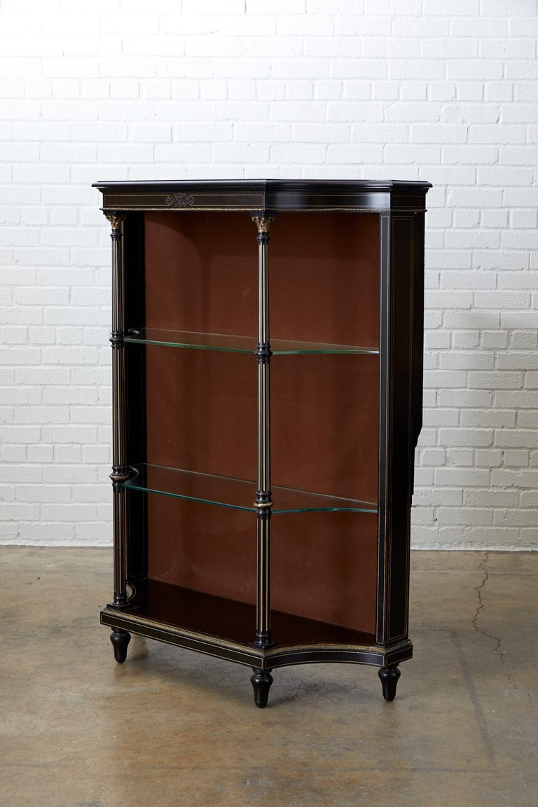 Dramatic 19th century French bookshelf or étagère featuring an ebonized case decorated with gilt string inlay. The piece has three glass shelves supported by bronze mounted neoclassical columns. Constructed in the French Napoleon III or Second
