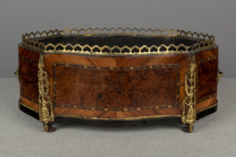 A 19th century Napoleon III marquetry jardinière made of mahogany with burl of walnut veneer and various inlay. Bronze-mounted with two handles, gallery and corner ornaments. Note: there is no zinc liner. A beautiful planter for the display of