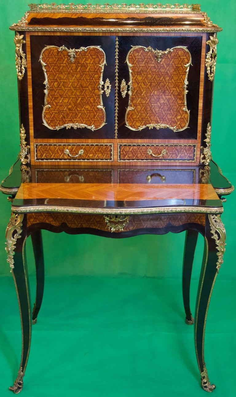 A French Bonheur du Jour, that is Napoleon III writing table, in rosewood and kingwood, with applications in gilded bronze and extractable writing top with two-panel doors with a single fixed shelf inside. 
