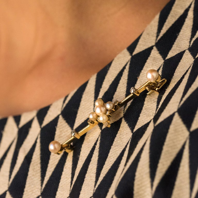 Brooch in 18 karats yellow gold. Elegant antique brooch, the center is composed by a cross motif set with natural pearls, separated and topped with rose- cut diamonds. The thin bar is adorned on both sides of antique-cut diamonds and finishes at