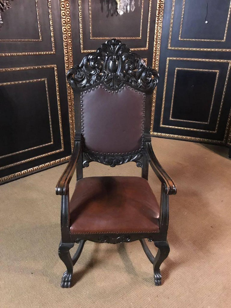 Solid oak. On four curved carved legs. Complete with rich carvings, flanked by two armrests. High backrest crowned by plastic carvings. The seat and back are leather covered in Classic design.  A good historical condition with a beautiful warm