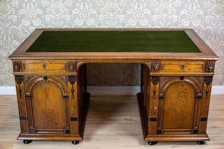 We present you a big man's desk, made of oak wood. It was manufactured in Q4 of the 19th century. This piece of furniture is composed of two separable cabinets, closed with a door, and a top with drawers incorporated into it. The door panels are