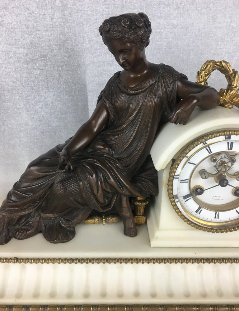 A fine 19th century French neoclassical marble and gilded bronze mantel clock with its original and exceptional movement is signed Finot a Versailles. The dial supporting a reclining bronze classical muse on a rectangular white Carrara marble base