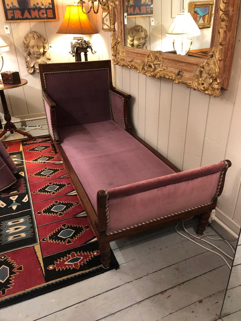 Romantic Parisian 19th century mahogany neoclassical daybed having dolphin decoration, turned feet, extension shelf on one end and aubergine velvet upholstery with silk rope detailing.