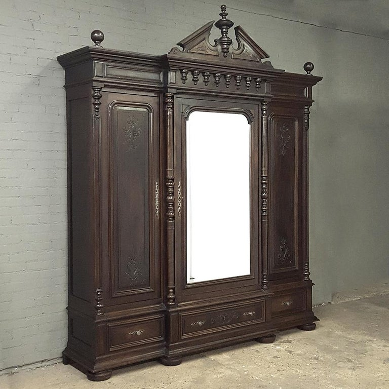 19th century neoclassical Revival three door armoire with full length beveled mirror and timeless styling will make the perfect centerpiece for your grandest room! Handcrafted from solid walnut, it features architecture inspired by ancient Greece,