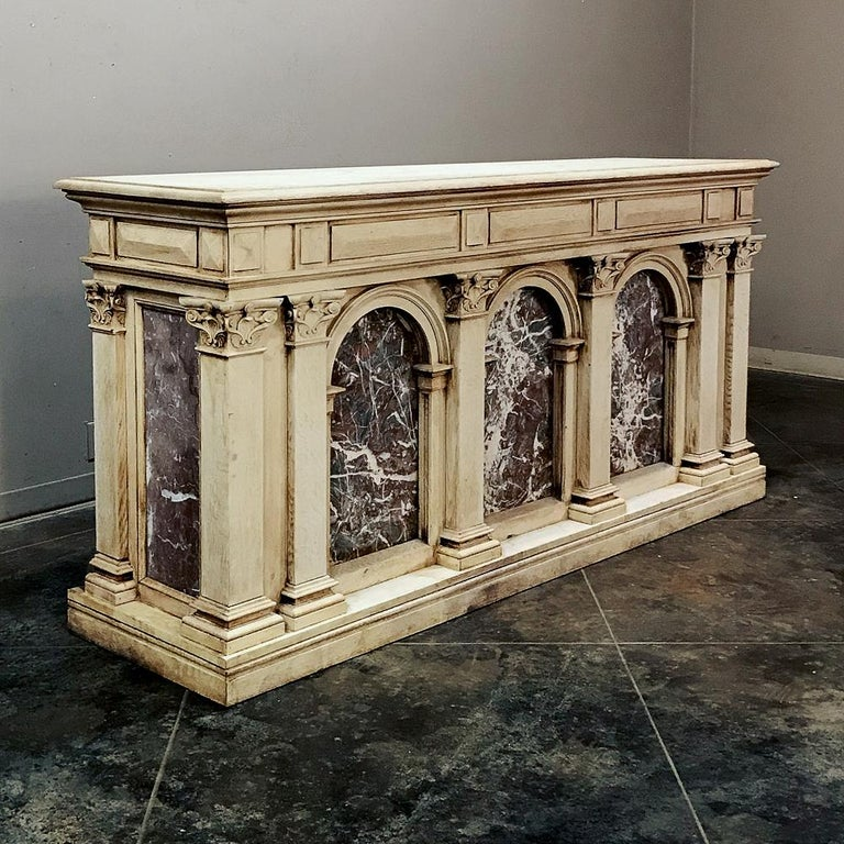 19th century neoclassical store counter, bar with marble inserts is a study in the epitome of ancient Greek and Roman architecture with Romanesque arches and fluted pilasters topped with Corinthian corbels surrounding luxuriously veined marble