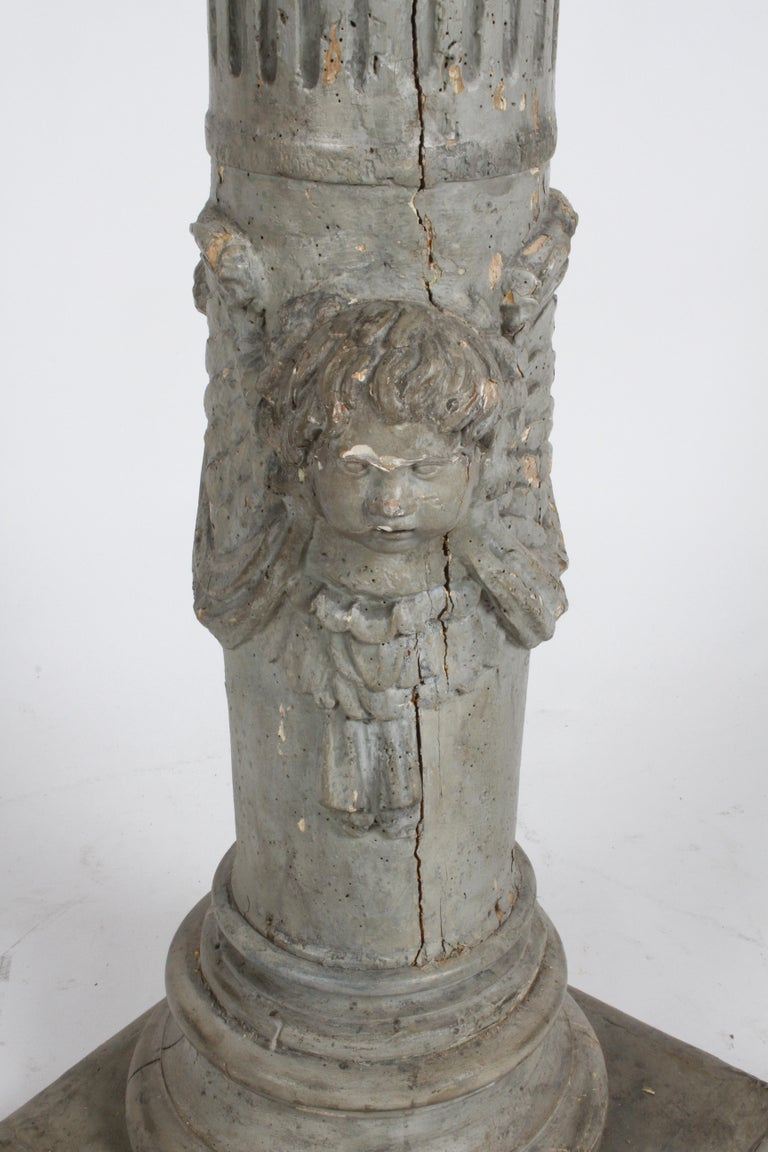 From a very prominent St.Louis estate this 19th century neoclassic style fluted wood decorative column with carved angel with wings, swag and drape, painted in a pewter gray paint. Loss of paint, old age cracks, insect bores, column on newer square