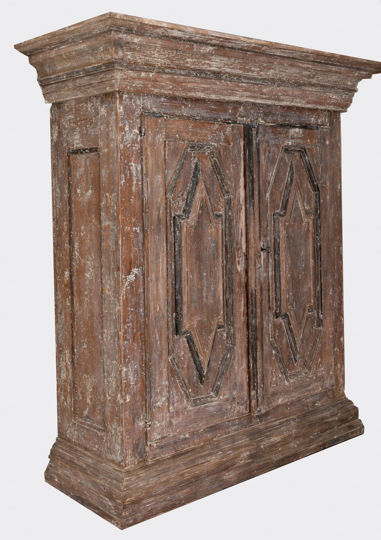 A 19th century Northern European cabinet in the Baroque style, beautifully carved and hand-scraped to the original exterior paint surface. Inside three fixed shelves. Original lock.