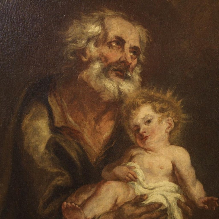 Antique Italian painting from the first half of the 19th century. Oil painting on canvas already backed again during the 20th century, depicting a subject of sacred art, St. Joseph and the infant Jesus of good pictorial quality. Carved and gilded