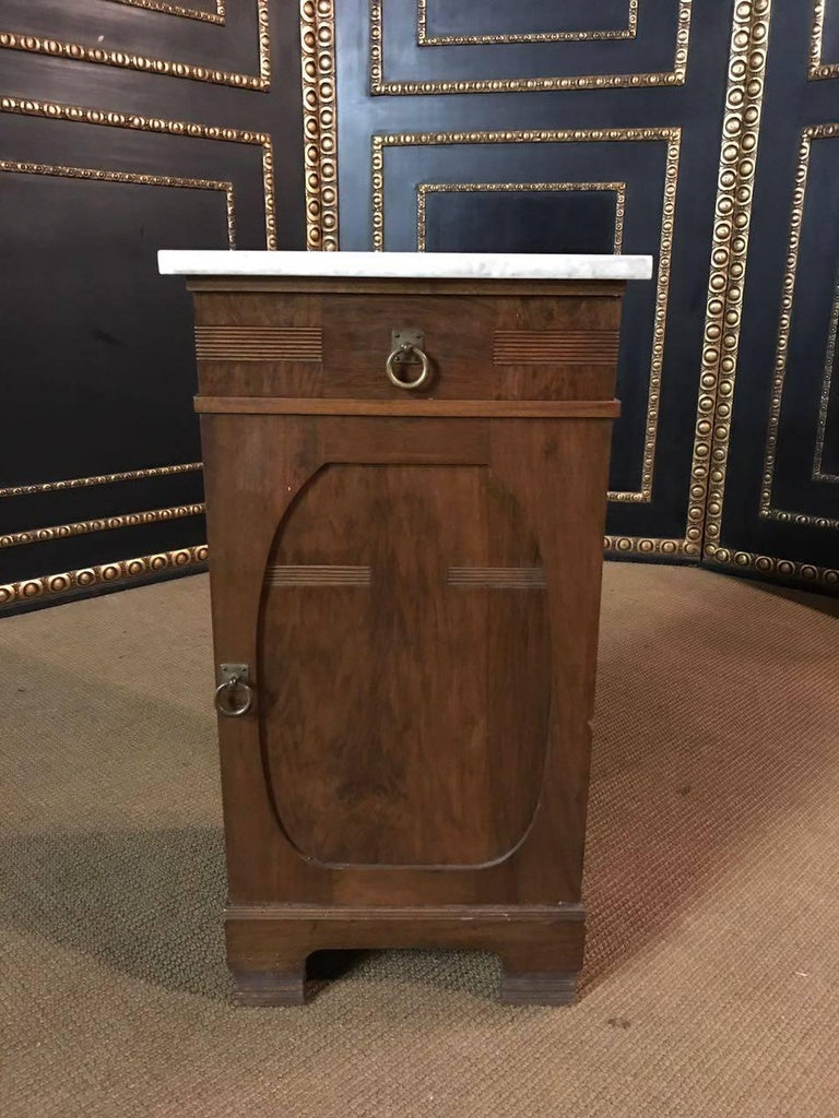 Solid wood with walnut veneer. High-rectangular body with a drawer and a door. Marble-top.  A good historical condition with a beautiful warm patina.