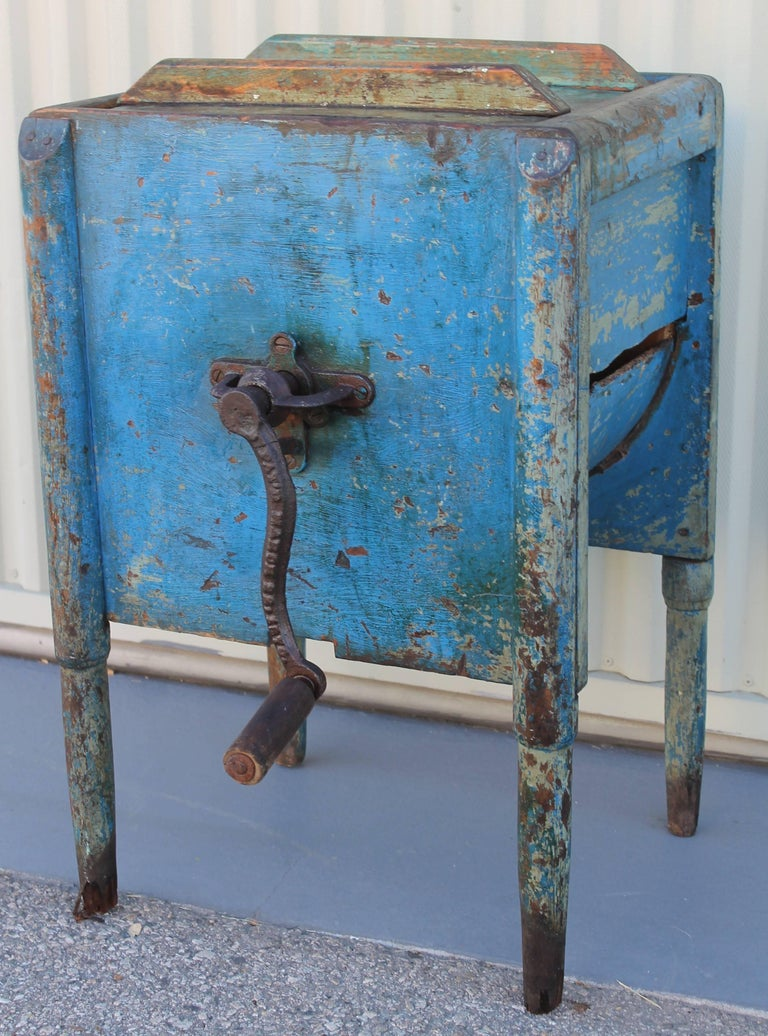 Fantastic original sky blue painted and handmade butter churn from New England. This worn and distressed churn is in working order with the original paddle guts. The handle is iron and original as well.