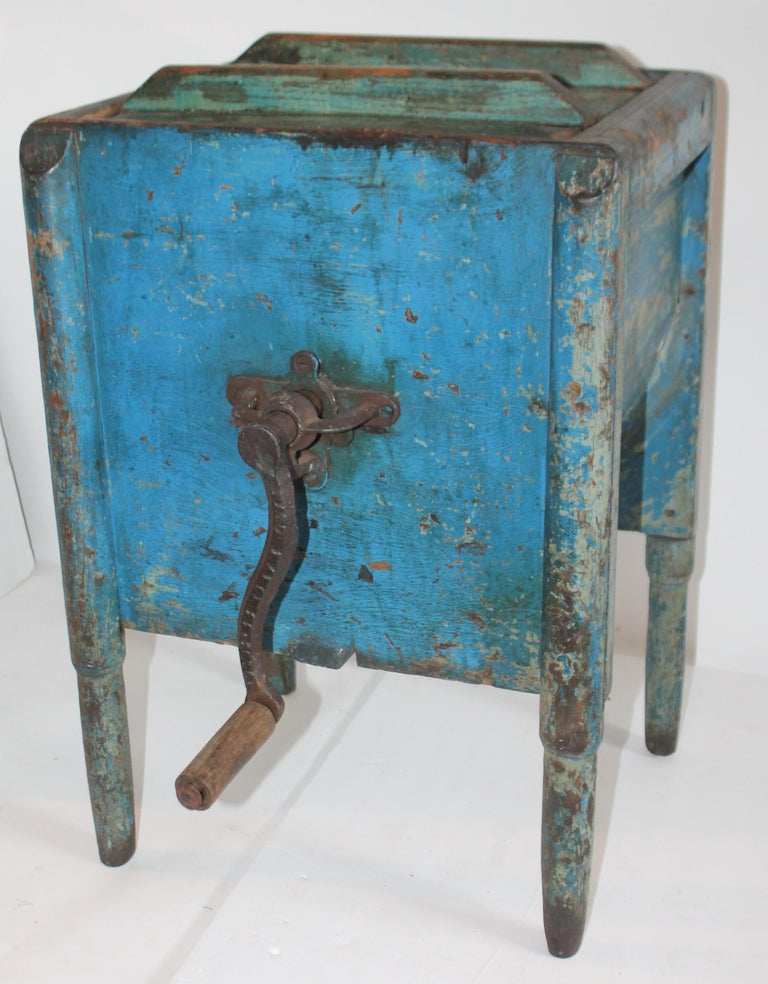 This 19th century original blue painted pencil post legs stand churn table. Great as a table by itself without side crank for churning butter. The lid is removable as well. Iron crank is on one side of the churn. This blue is the magical color and