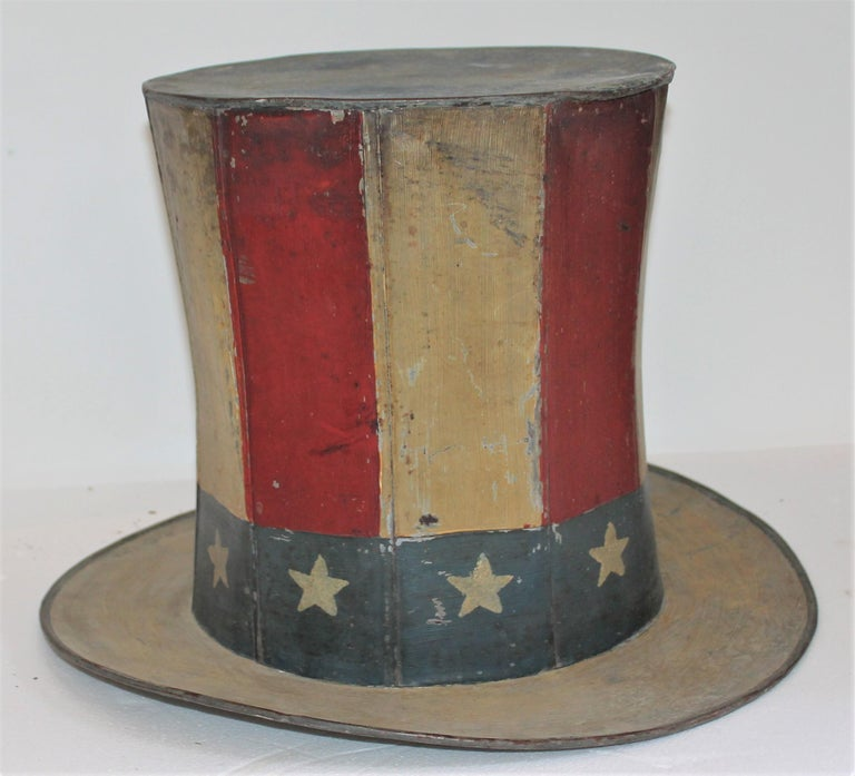 This original painted tin trade sign of a patriotic motif. Looks like a Uncle Sam's top hat. This hand made and painted tin trade sign is signed by the maker and dated 1881.  Interior diameter measures - 10inches.