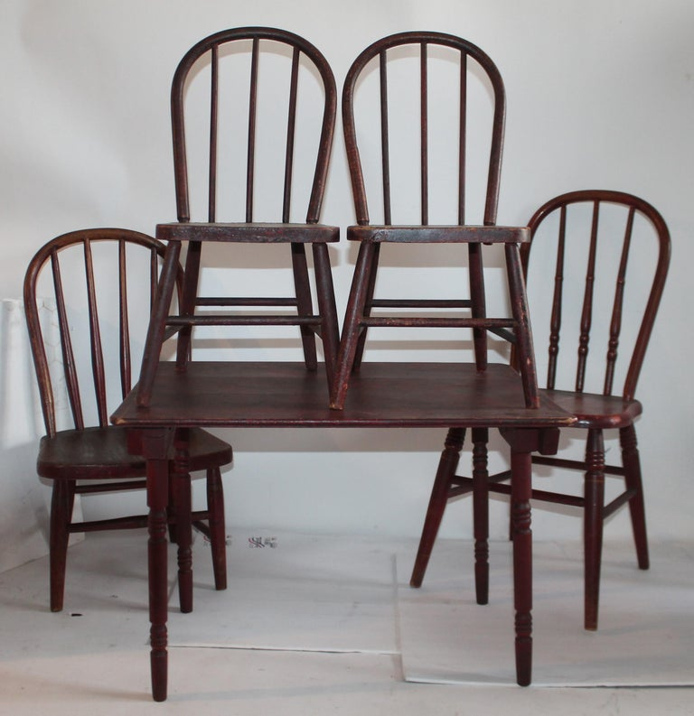 Fantastic 19th century child's original red with mustard pin striping paint folding table and a collection of four children's chairs in a wonderful old patina. The condition is very good and sturdy. Great for child's room or in a cabin.   Table
