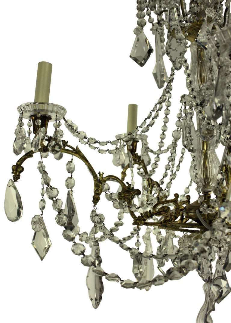 A French chandelier of five branches in ormolu and hung with cut-glass by Baccarat of Paris, signed.