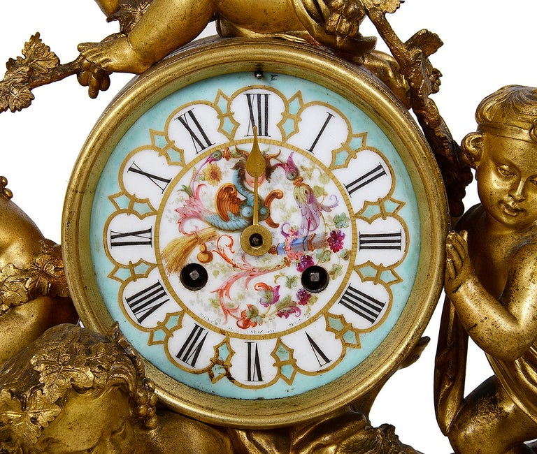 An enchanting 19th century Louis XVI style gilded Bacchus influenced ormolu mantel (fireplace) clock depicting three putti rolling a barrel on the back of a cloven hoofed putti. The hand painted porcelain clock face within the barrel has an eight