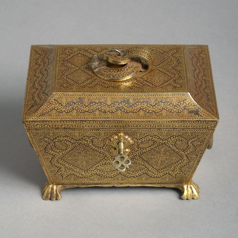 The steel sarcophagus form with fine, all-over Koftgari decoration in yellow gold. The hinged, tented lid with central buckle decoration a above a tapering body with ring handles to the sides and raised on braganza feet. Complete with original key.