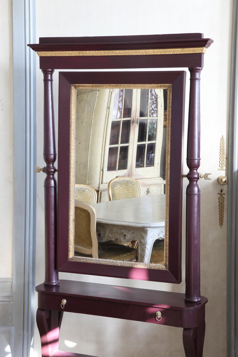 An elegant, 19th century, Italian cheval mirror made in both solid and veneered mahogany wood with hand carved giltwood mouldings and ormolu fittings. Fitted with neat drawer at the mirror. Painted in a deep purple lacquer.