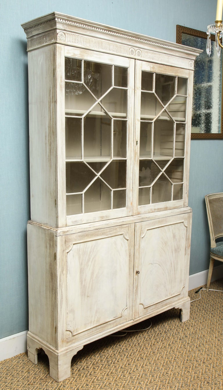 This painted English cabinet has a quiet elegance about it. The piece features two glazed mullioned doors opening to an upper cupboard over two lower paneled doors and two lower storage shelves. Raised on bracket feet, the cabinet features a dental