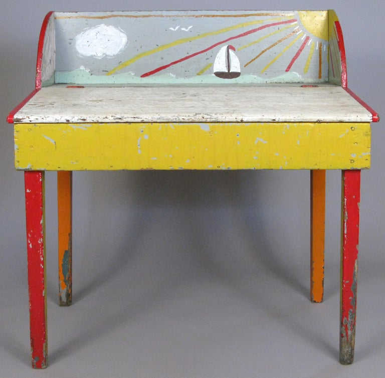 A very charming antique 19th century slant front pine desk found in Cape Cod, MA. Entirely hand painted in colors of red, yellow, orange, and white, with a whimsical ocean scene of a sailboat and the sun. Has a hinged work surface.