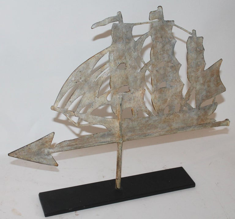 This wonderful painted sailing ship weathervane has a great worn patina on the painted cream surface. It is on a custom-made black iron stand. The condition is very good.