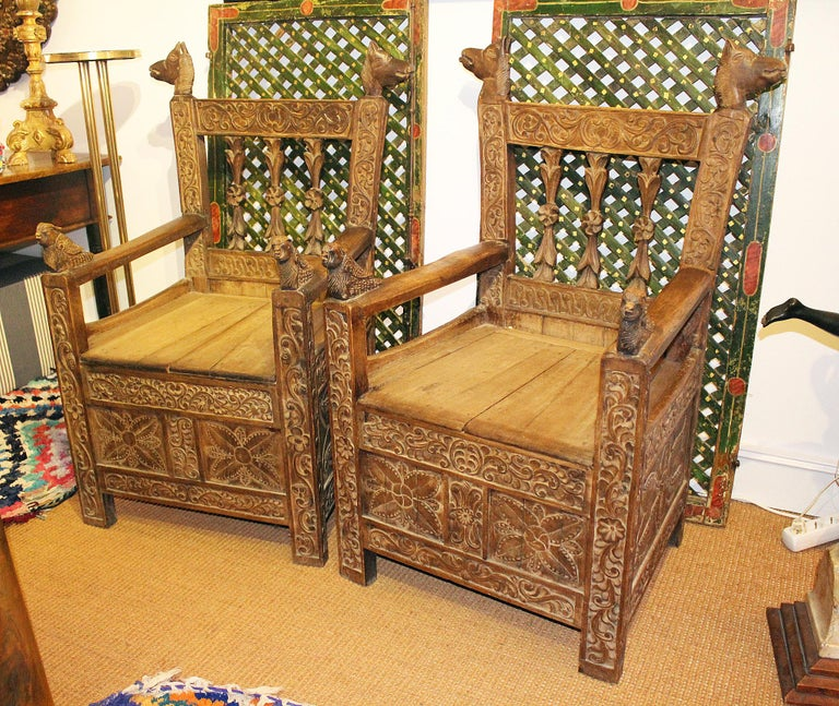 19th century pair of Bolivian hand carved wooden armchairs, decorated with geometric motifs and animals on arm and backrest.
