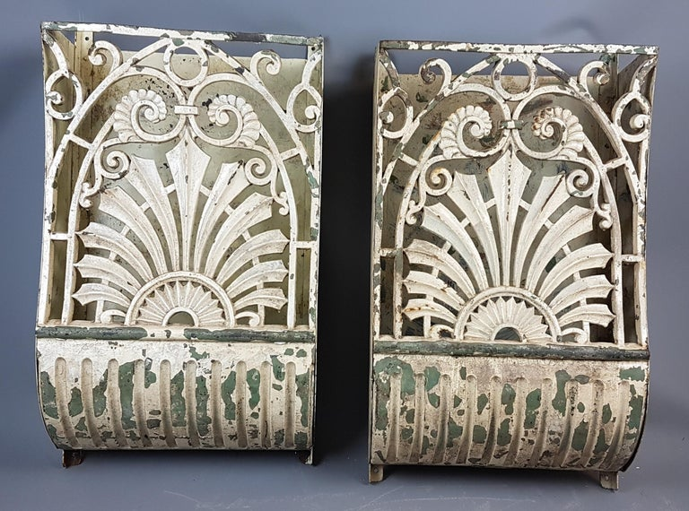 This is a great and very decorative pair of 19th century cast iron wall-mounted pockets that are perfect for unique consoles with lighting inside.  They have layers of old paint that has given them a desirable appearance with the base layer being