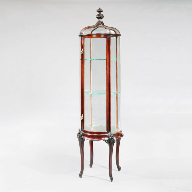 A pair of circular display cabinets Constructed in a well patinated mahogany; of freestanding circular form, rising from four swept cabriole legs, the five upright ogee form ribs, carved with foliate bosses at the horizontal interstices, enclosing