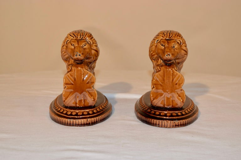 19th century pair of pottery figures of lions resting on English shields. They are sitting on molded bases which are beaded around the platforms. Wonderful color. No maker's mark.