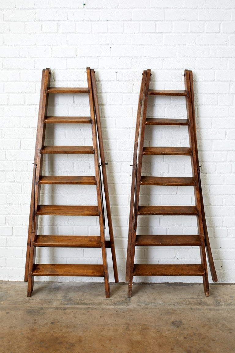 Handsome pair of late 19th century French country folding library ladders. Featuring a handcrafted design with seven rungs or steps and iron hardware. From an estate in Santa Barbara, CA.