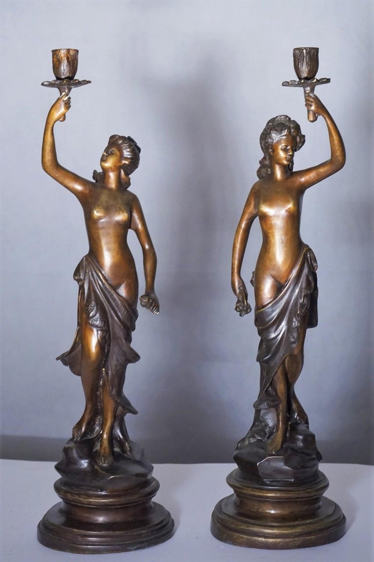 A pair of heavy patinated bronze sculpture candelabra, France, mid-19th century. Two female sculptures holding a candleholder raised on a bronze circular base, signed by the artist. Measures: Height 21 in / 54 cm Base diameter 6 in / 15 cm.