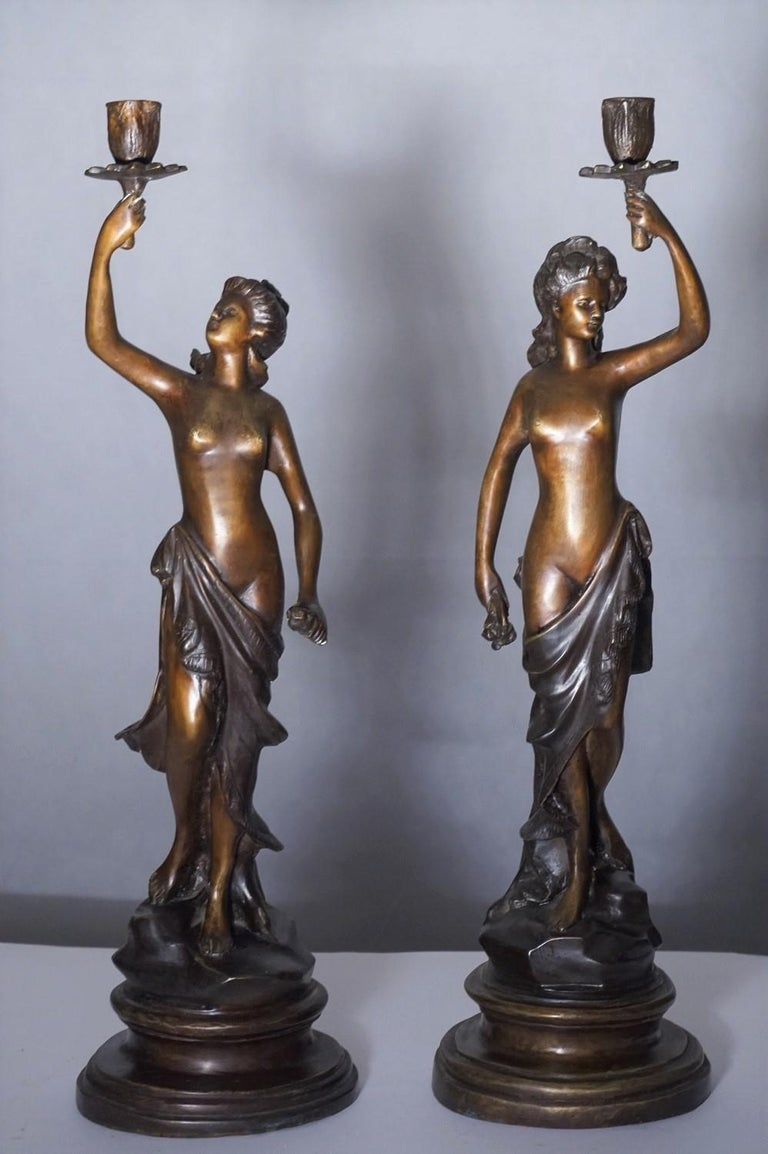 A pair of heavy patinated  bronze sculpture candelabra, France mid-19th century. Two female sculptures holding a candleholder raised on a bronze circular base, signed by the artist. Measures: Height: 21 in / 54 cm Base Diameter: 6 in / 15 cm.