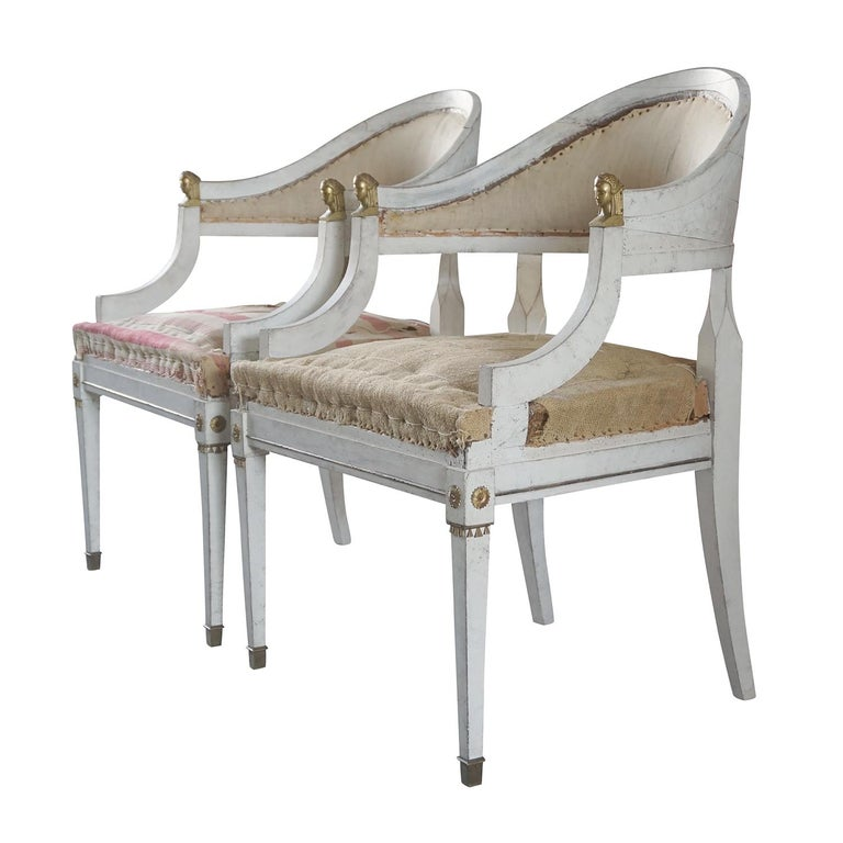 A unique Swedish Gustavian pair of armchairs made of wood and bronze. The hand carved side chairs are in good condition, detailed in the neoclassical Greek style, enhanced by very detailed carvings. Two of the wooden legs are inserted into metal