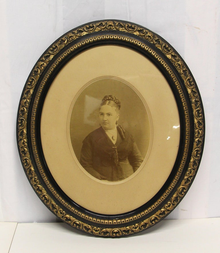 19th century sepia oval matted early photographic portraits of a man and a woman in decorative black and gold oval frames. The frames themselves are in very good vintage condition with scroll and egg and dart details. One frame is missing glass and