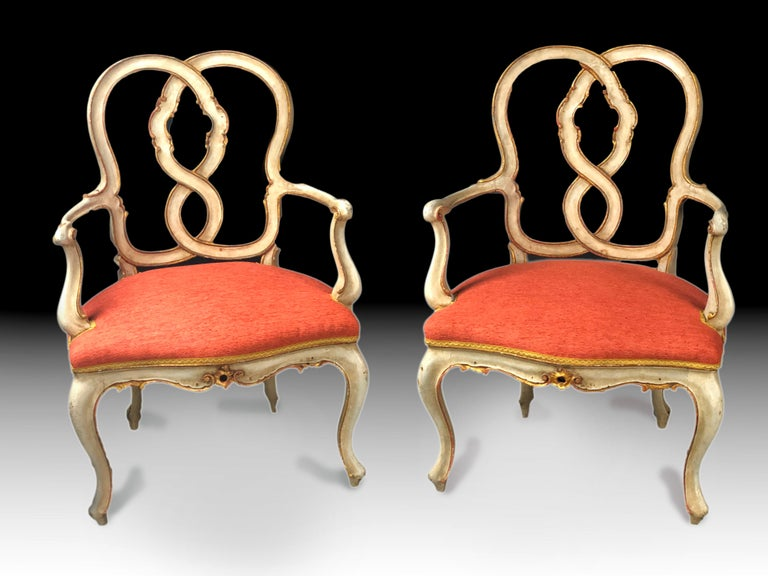 Impressive and rare pair of early 19th century Italian armchairs, most probably Venetian, painted in their original light grey color, parcel gilt and with original patina and wear through their 2 centuries of existence. Their back with interlaced