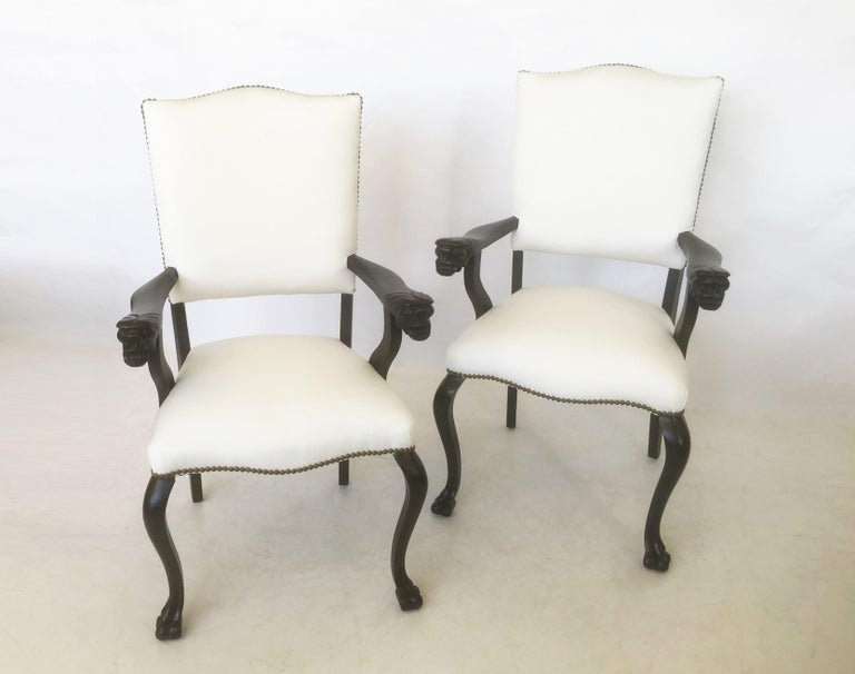 An attractive pair of restored carved walnut armchairs, Italy, circa 19th century. Each chair features a curved crest rail, padded back and seat covered in a new sturdy cotton fabric and bronze nailhead trim. Two wooden open arms adorned with carved