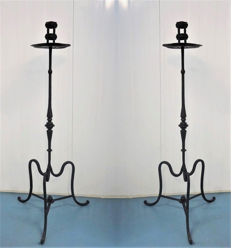 Great pair of Italian Renaissance Revival wrought iron church torchères raised on a large tripod base, early 19th-century. The candleholders are finely handcrafted with elegant detailing and are black painted. Both pieces are in good condition, with