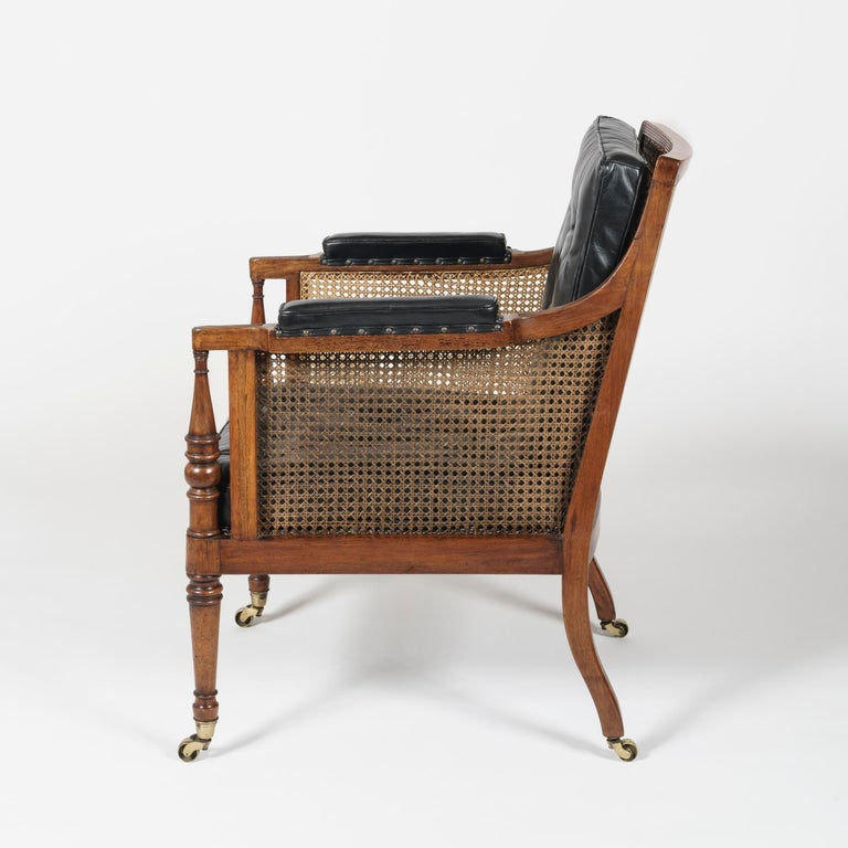 A good pair of library bergère armchairs of the Regency Period Attributed to Gillows  Constructed in Honduras mahogany, rising from brass castor shod feet, the front legs ring-turned and tapering, having reeded downswept arms and a conforming